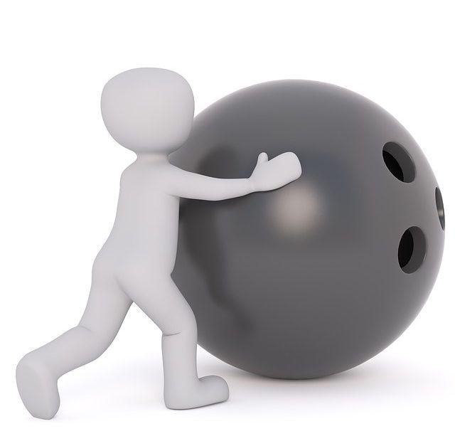 Litet barn knuffar ett enormt bowlingklot